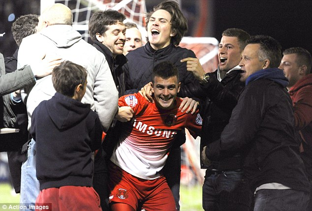 All in: Fans celebrate Leyton Orient's victory over Peterborough with their first goal scorer Dean Cox