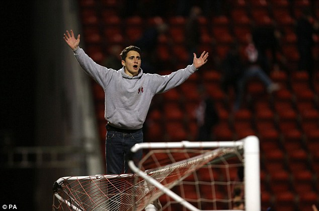 Nothing but net: An Orient supporter sings at the top of his lungs on the top of goal