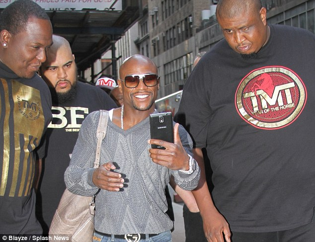Friends in high places: Mayweather was accompanied on the trip by a burly looking security team