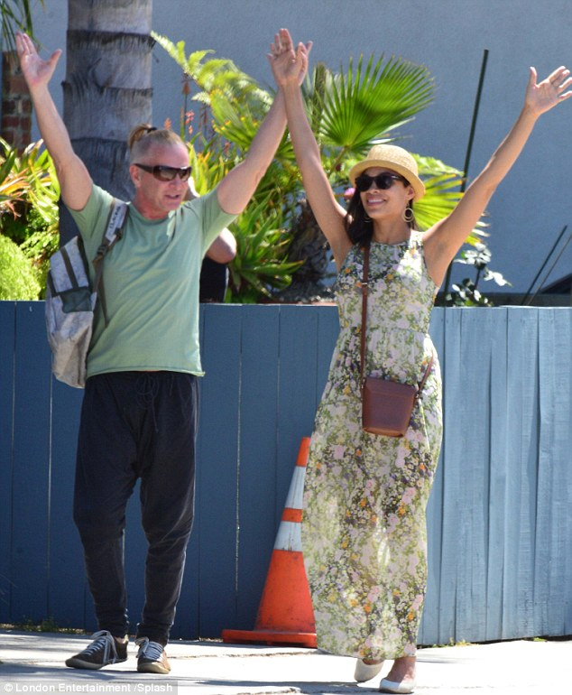 A salute to the sun: Rosario Dawson and her male pal were in good cheer as they performed the curious salutation in balmy Venice Beach on Tuesday