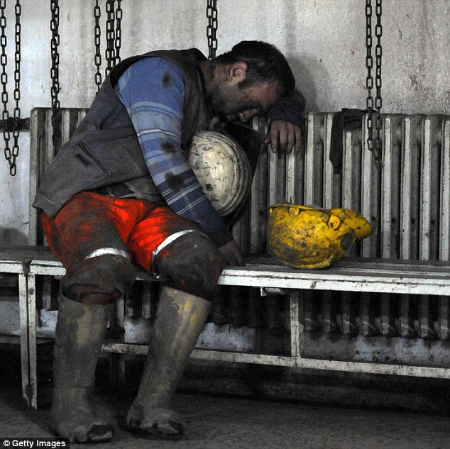 A miner sits on a bench in a state of exhaustion