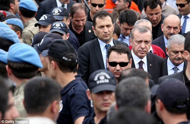 Sombre: Turkish Prime Minister Tayyip Erdogan visits the scene