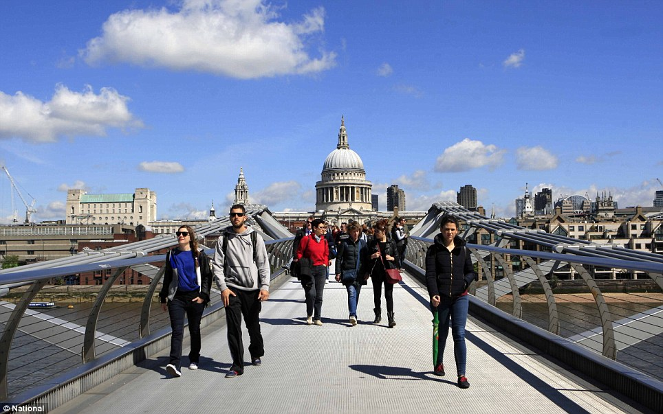Crossover: Locals and tourists enjoy the sunshine as they cross the Millennium Bridge in front of St Paul's Cathedral in central London this morning. Temperatures are set to rise dramatically at the weekend, after a period of unsettled weather