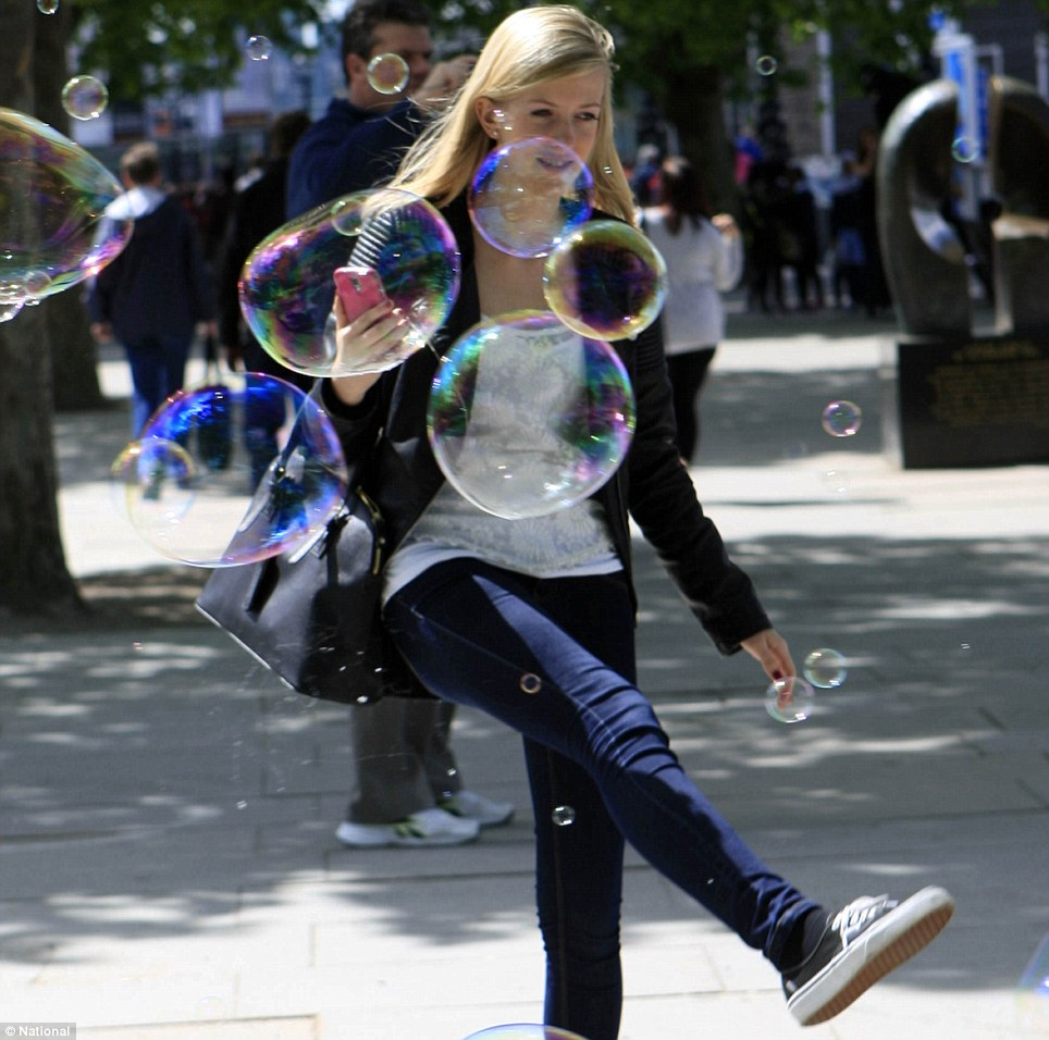 Having a bubble: A young woman smiles as she kicks bubbles while walking on London's Southbank. Locals and tourists spent the day soaking up the sun in the capital