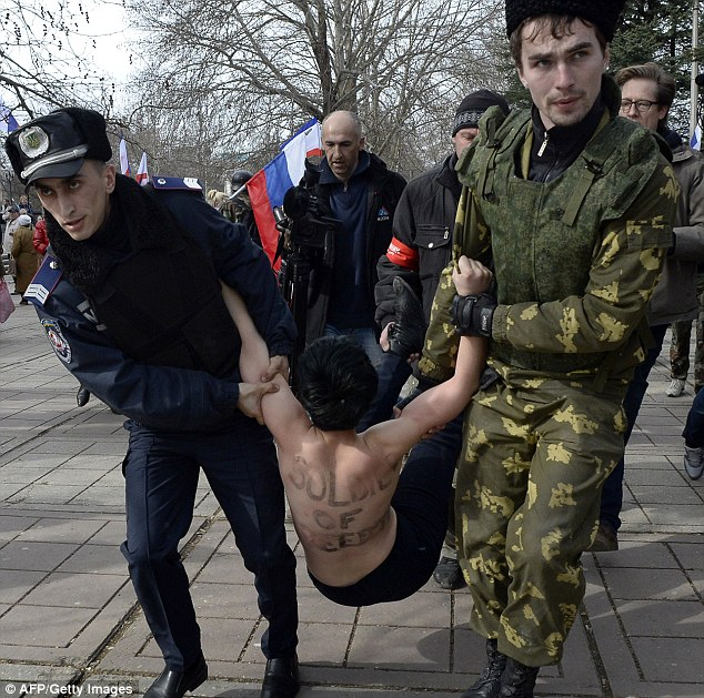 Protest: A FEMEN activist is dragged away after a protest during a pro-Russia rally in Simferopol in Crimea