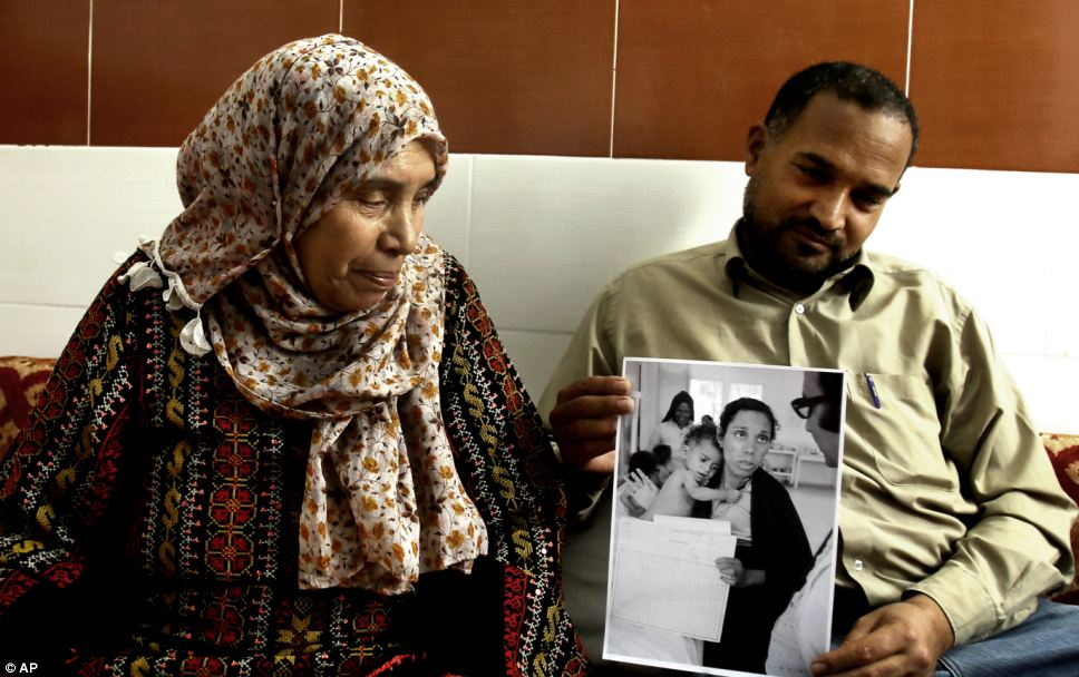 That was then, this is now: Palestinian refugees Fathiyeh Sattari, 62, and her son Hassan, 40, look at their photograph that was taken at the Rafah UNRWA clinic in 1975, at their family home in Rafah Refugee Camp, the southern Gaza Strip