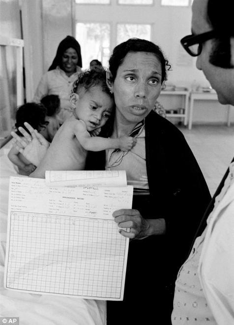 In this 1975 photo from the U.N. Relief and Works Agency, UNRWA, archive, Fathiyeh Sattari, a worried Palestinian mother talks to a doctor about her underweight child, Hassan. He is now 40 and a father of five