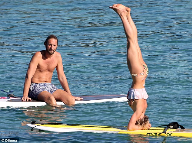 Strike a pose: Millionaire tycoon Justin Hemmes and his yoga teacher girlfriend Carla McKinnon enjoy a spot of paddleboarding and head standing at Coogee Beach on Thursday afternoon