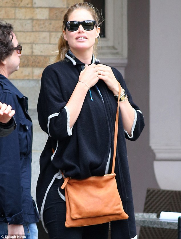 Under wraps: Doutzen Kroes covered up her baby belly in a loose black sweater as she left a restaurant with friends in New York City Wednesday