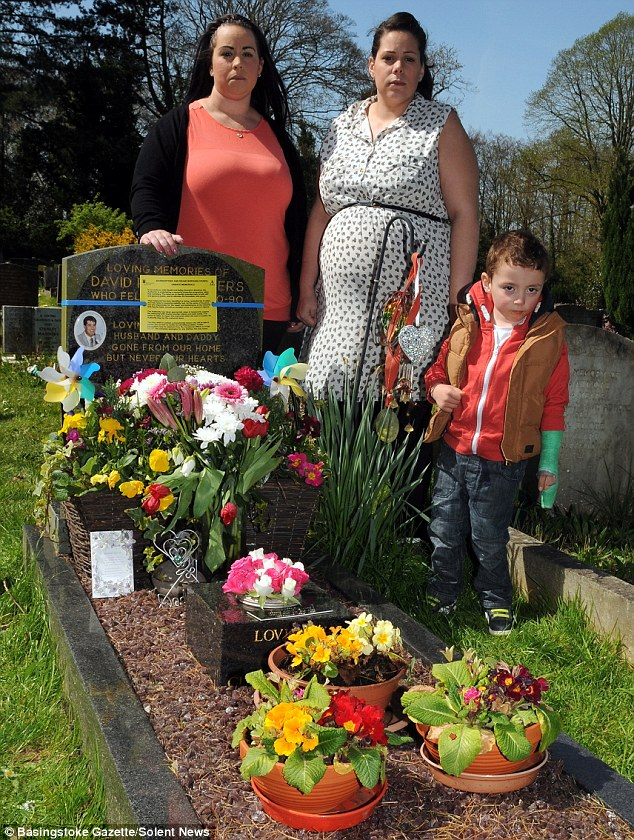 Yellow sign: Claire Ridgers-Smith (left) with her sister Davee Ridgers and her son Charlie Ridgers, by David Ridgers's gravestone at Worting Road Cemetery in Basingstoke, Hampshire