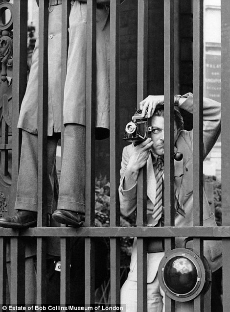 A photographer taking a picture through the railings at Admiralty Arch the day before the Coronation of Queen Elizabeth II in June 1953