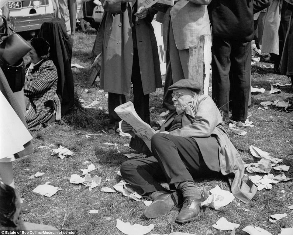 A day at the races: A spectator reads a newspaper at Epsom Downs Racecourse, Surrey, on Derby Day in around 1960. Mr Collins also took his work outside the city