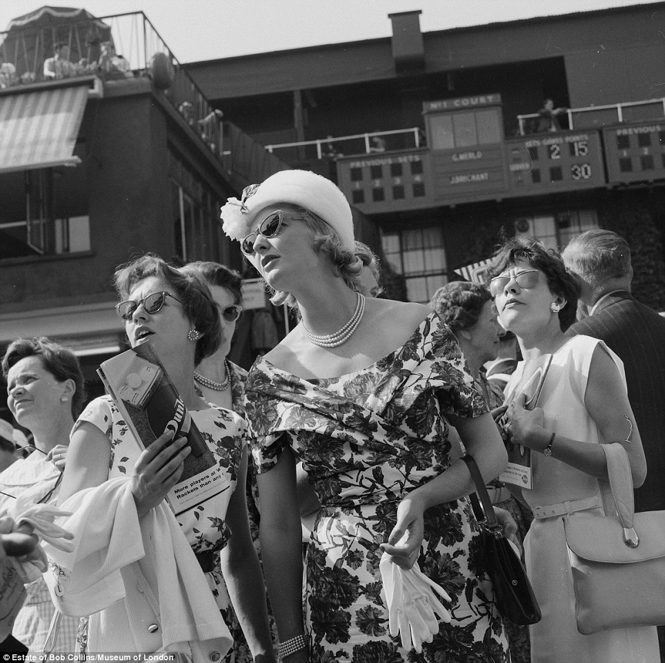 A very English day out: Well-dressed women attending the All England Lawn Tennis and Croquet Club Championships at Wimbledon in 1960 - and all looking at the scores