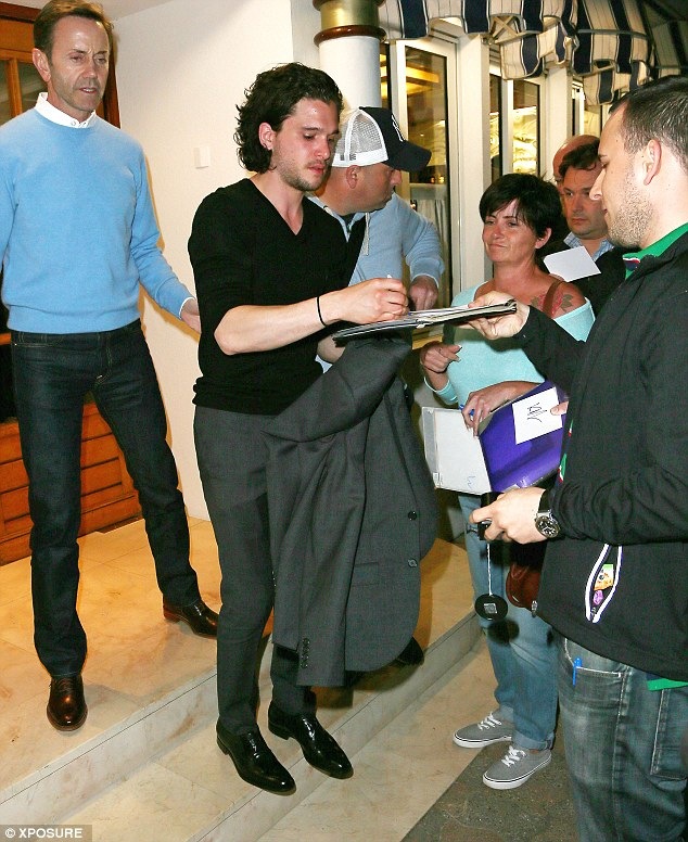 Keeping watch: Kit signs autographs for waiting fans outside the Tetou restaurant in Golfe Juan