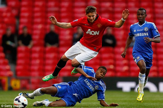 Getting stuck in: Charly Musonda slide tackles Guillermo Varela of Man United during the Under 21 final at Old Trafford
