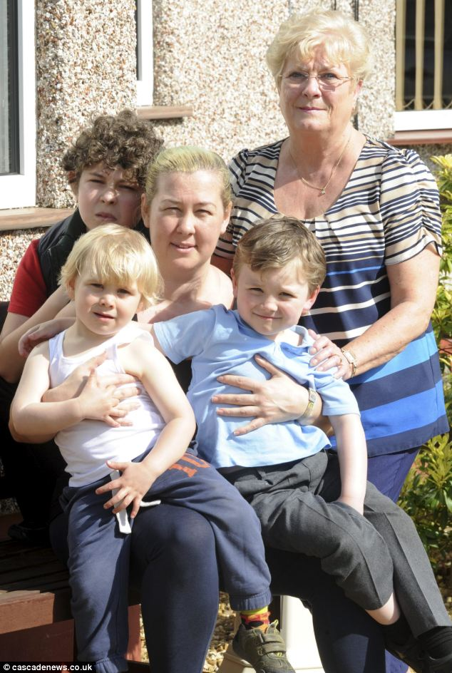 Sally Randall, centre, with her mother, Lavinia Crisp and her children, James, 13, behind her and Joe, five, and Beaudie, three sitting on her knees. She was hauled to court after the family went on holiday to Majorca during term time with terminally ill grandfather Graham Crisp