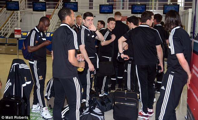 Waiting game: Hull players stand and wait with their luggage before boarding a flight to London