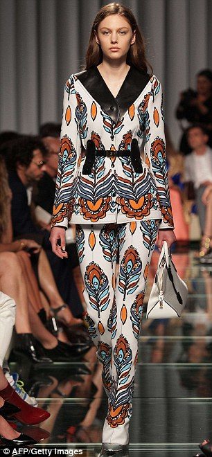 On the catwalk: Models took to the catwalk in vibrant and patterned trouser suits (pictured), while clutching pale statement handbags