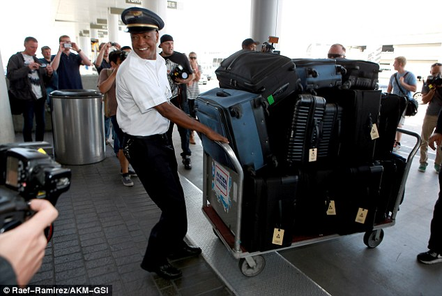 Heavy lifting: The reality star had a jaw dropping 12 bags in tow, which were stacked up on a huge trolley and left top an Air France employee to struggle with