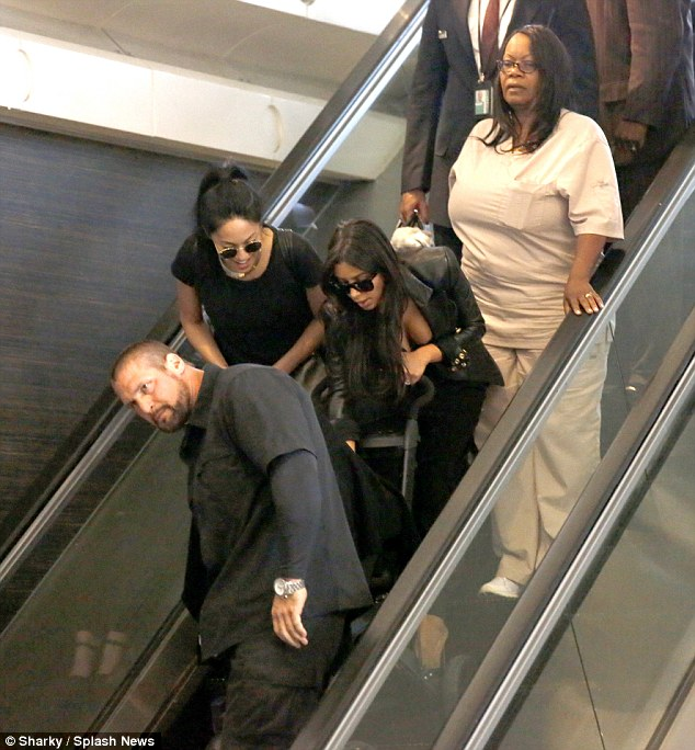Help! The reality star cooed over her little one as she was assisted on an escalator with her pram