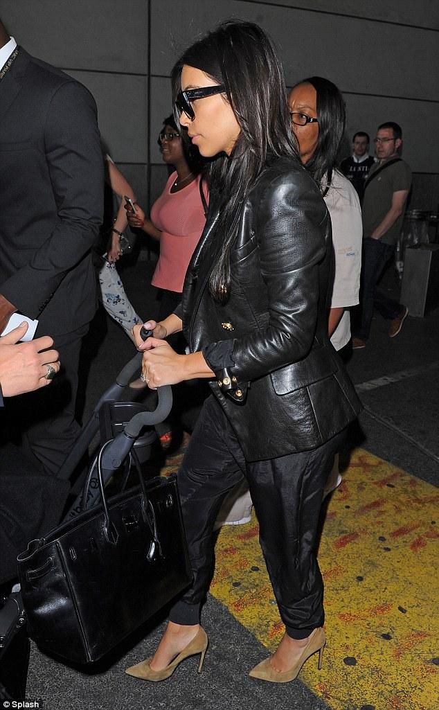 Kim balanced her Hermes Birkin bag on the handle of the pram
