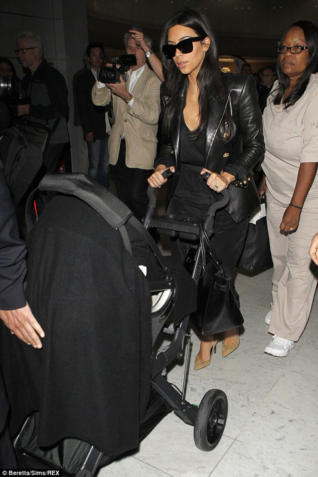 Time for a nap: Kim Kardashian looks a little weary as she touches down in Charles De Gaulle airport in Paris on Sunday