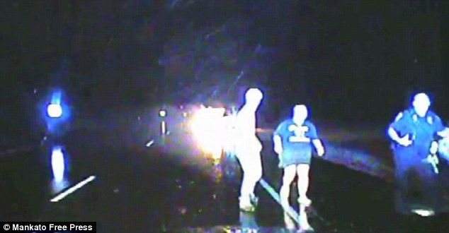 Safe and sound: Michael Smith (left), Anna Smith (center), and Officer BUrdan (right) are seen fleeing the burning vehicle back to the safety of the squad car