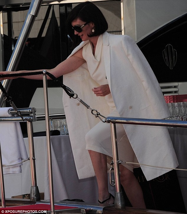 On-board: Paz's chic ensemble included a long white coat, with just a single button, and simple drop earrings