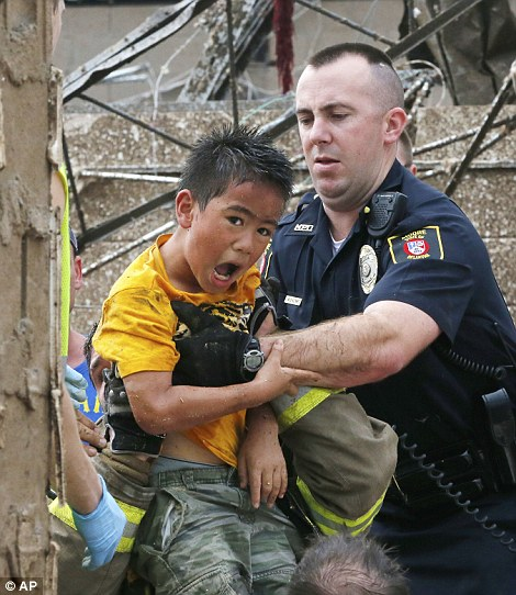 Hope: In this May 20, 2013 file photo, a boy is pulled from beneath a collapsed wall at the Plaza Towers Elementary School following a tornado in Moore, Okla. (AP Photo/Sue Ogrocki, File)