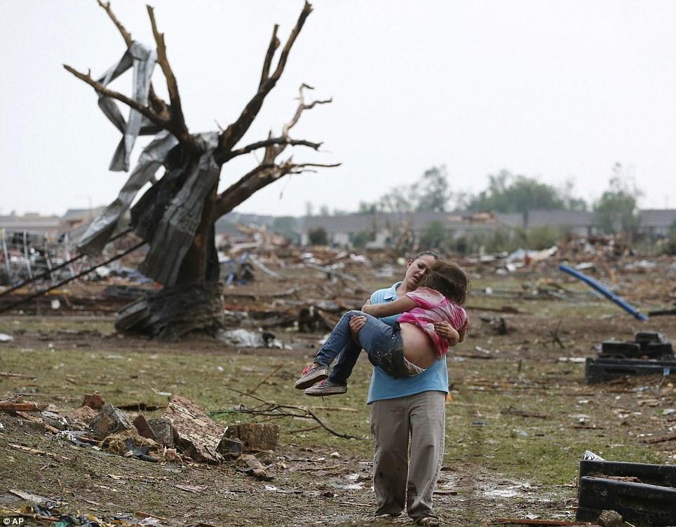 Heartbreaking relief: LaTisha Garcia carries her 8-year-old daughter, Jazmin Rodriguez, near Plaza Towers Elementary School after the tornado carved its way through Moore leaving little of the school and neighborhood