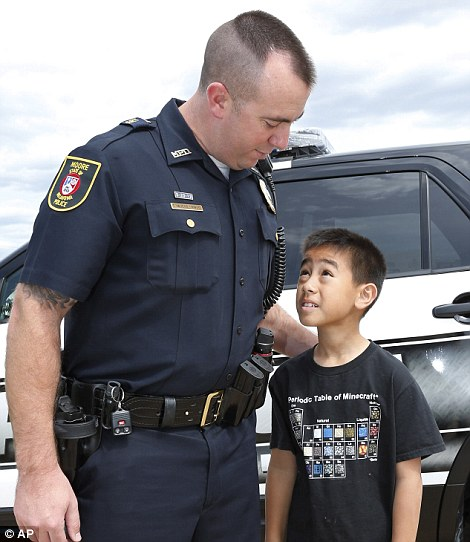 Safe: Kai Heuangpraseuth, (left and right), looks up at Moore police officer Travis Muehlenweg after they met one year on after the child was pulled from the rubble of the Plaza Elementary school