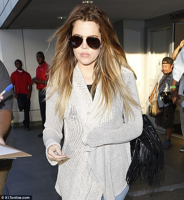Comfort first: The Keeping Up With The Kardashians star was dressed down as she headed through the terminal, wrapped up in a beige knit cardigan, teamed with tight pale blue skinny jeans