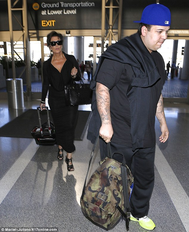 Runs in the family: Rob wore all black just like his mother as he strode into the busy landing place