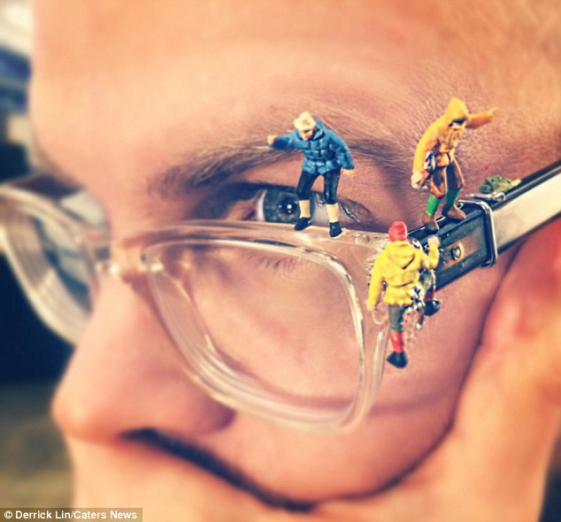 Sometimes it takes a lot for ideas to be noticed: Mini figurines balance on the glasses of a co-worker