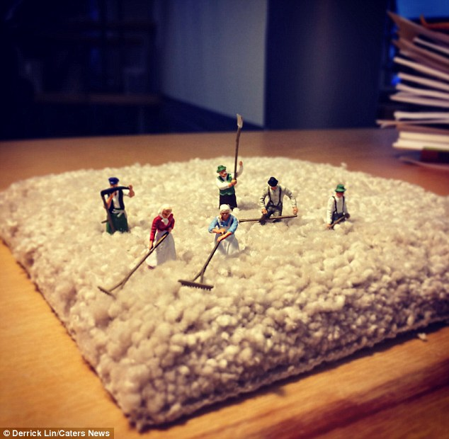 Rug's life: Mini figurines appearing to farm a piece of fabric on Mr Lin's desk - illustrating the fact that they always get to know their clients' products
