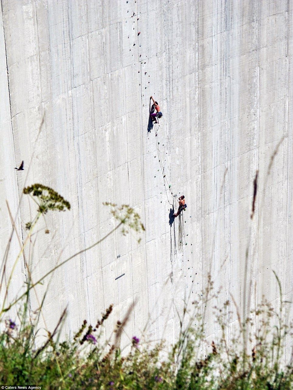 'Are we there yet?': Daredevils mid-way through the 540ft climb of the 540ft-high dam