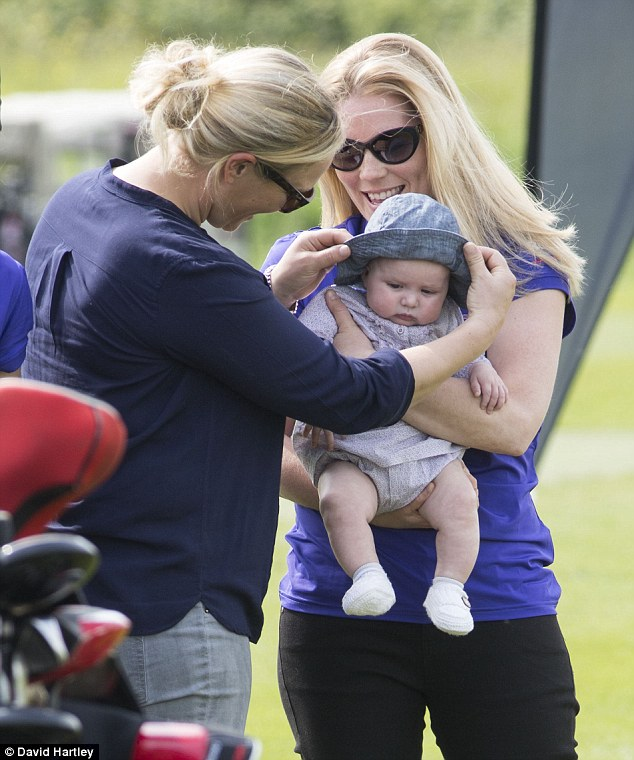 Zara lifts the hat out of her daughter's eyes as she's held by her sister-in-law Autumn Phillips while at the driving range as Mike Tindall hosted golf event in May