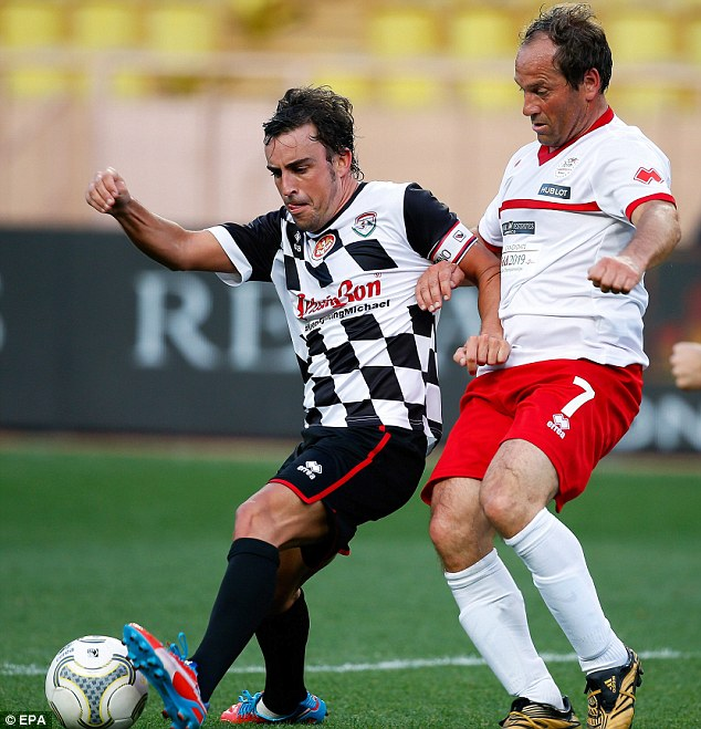 Stuck in: Alonso challenges an opposing player as the Formula One players got ready for the Grand Prix
