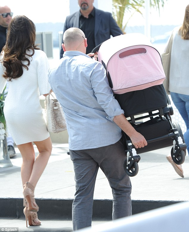You do the honours: A burly minder ghefts Tamara's empty pushchair up a flight of steps on the Cannes Croisette