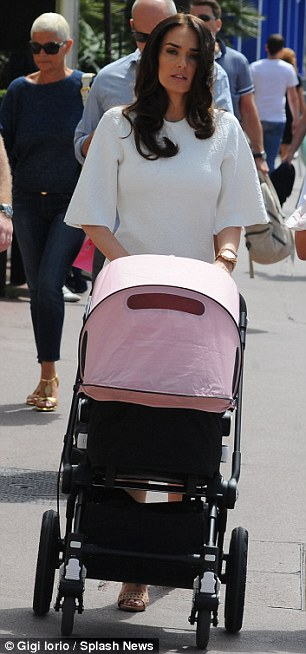 Doting mother: Tamara pushes the empty pushchair across the Croisette during a morning stroll with her family ahead of a photo-shoot on Wednesday
