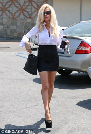 Finishing touches: The platinum blonde wore her hair down and curled at the ends and showed off a simple french manicure while holding onto a bottle of Pepsi cola and her keys as she strutted to her car