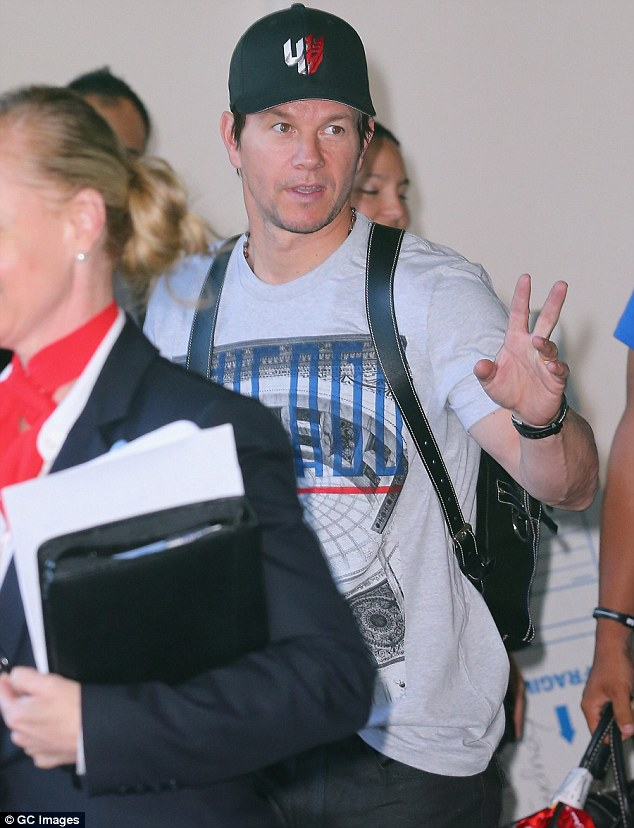 Peace out: He waved to photographers and starstruck fans as he made his way through the international terminal