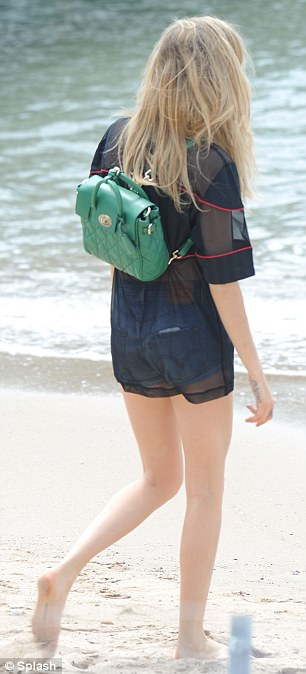 Relaxed: Cara looked at home while wandering around Cannes