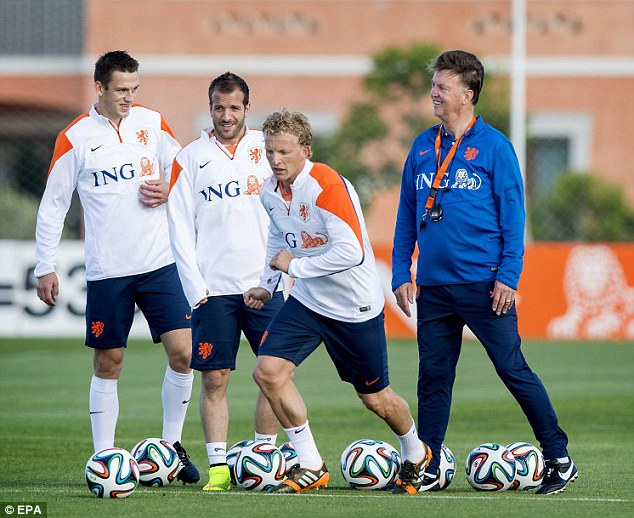 All smiles: Van Gaal looks on as former Premier League stars Rafael van der Vaart (second left) and Dirk Kuyt (second right) take part in a Holland training session on Wednesday