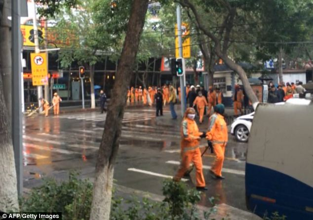 Cleaners clear the street in Urumqi where the bloody attack unfolded