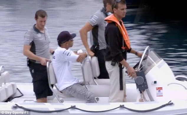 Making a dash for it: Hamilton arrives on boat just moments before the start of Friday's opening session