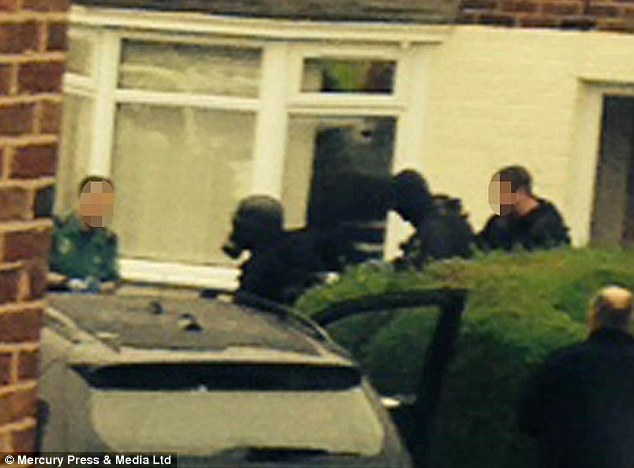 Drama: Armed police in the garden of a Liverpool after they stormed it and shot a man inside after a 40 minute stand off