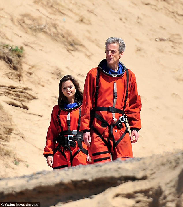 The future's ORANGE! Dr Who's Peter Capaldi and travel companion Jenna Coleman were seen wearing brightly coloured spacesuits as they filmed on a Welsh beach on Wednesday