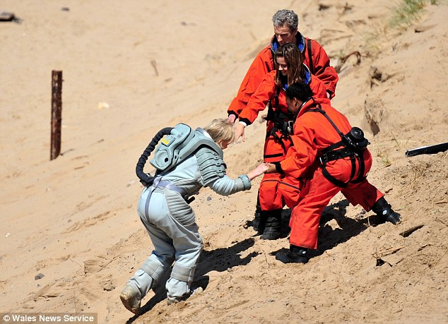 Helping hand: The actor was joined on the sands by glamorous Jenna, 28, who plays companion Clara Oswald and two other companions