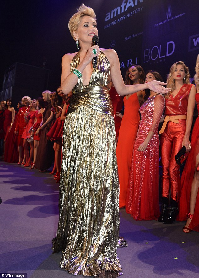 Golden girl: Sharon Stone wore a plunging gold dress as she presented the stunning modes